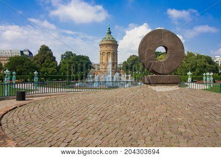 Wheel Sculpture Against Fountains At Friedrichsplatz With Mannheim Water Tower