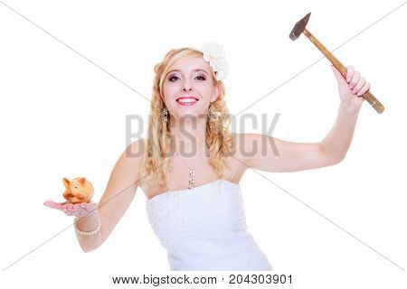 Household savings cash after wedding concept. Bride wearing white dress trying to break piggy bank with hammer