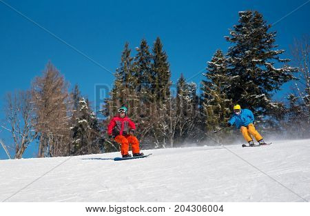 Male Snowboarder Riding On The Snowy Slope And Professional Skier Cameraman Shooting Snowboarder By
