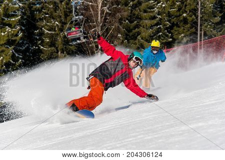 Active People Enjoy Riding And Skiing In The Mountains At Winter Ski Resort. Male Snowboarder Skiing