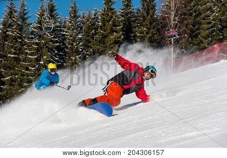 Male Snowboarder Skiing On The Snowy Slope And Professional Skier Cameraman Shooting Him By Action C