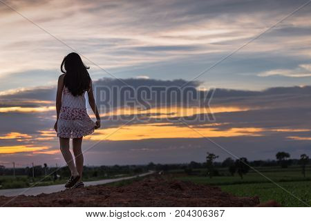 Beautiful Asian Woman Standing On The .mound With Sunset