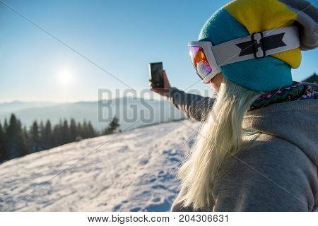 Woman Snowboarder Relaxing After Snowboarding, Taking Photos Of Winter Nature In The Mountains Using