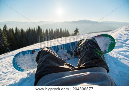 Point Of View Shot Of A Snowboarder Lying On The Snow On The Slope In The Morning, Relaxing After Sk