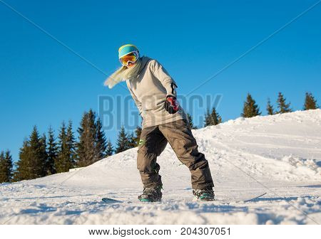 Full Length Shot Of A Blonde Haired Female Snowboarder Riding In The Mountains On A Beautiful Sunny