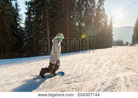 Young Woman Snowboarding On The Slope On A Beautiful Winter Sunny Evening Copyspace Sunlight Sunset