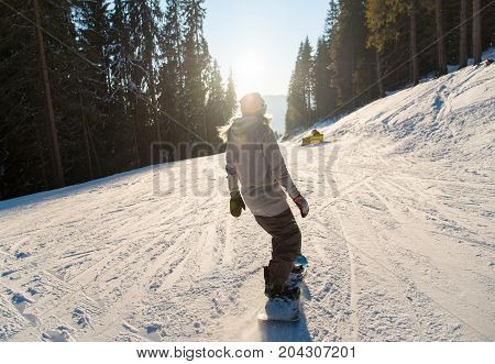Rearview Shot Of A Snowboarder Riding The Slope In The Mountains On A Beautiful Winter Sunny Day Sun