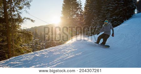 Horizontal Shot Of A Female Snowboarder Riding Downhill On Snowy Slope In The Evening Copyspace Scen
