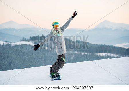Shot Of A Cheerful Female Snowboarder Having Fun While Riding In The Mountains Posing On The Slope C