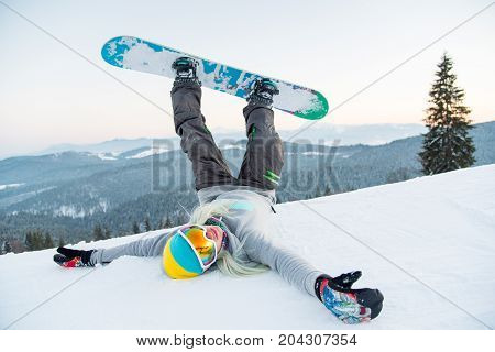 Excited Young Snowboarder Woman Having Fun On The Slope Lying On The Snow With Her Legs In The Air H