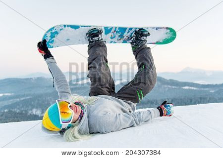 Excited Young Snowboarder Woman Having Fun On The Slope, Lying On The Snow With Her Legs In The Air