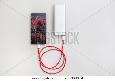 Smartphone charging with power bank on white table