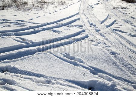 traces of the car in the snow in winter