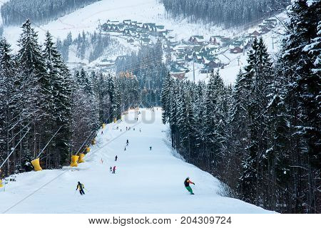 Winter Evening Landscape Ski Slope Of Resort Bukovel With Skiers And Snowboarders Against Snow-cover