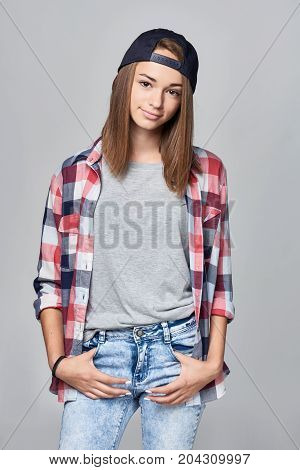 Teen girl standing relaxed with hands in pockets over grey background