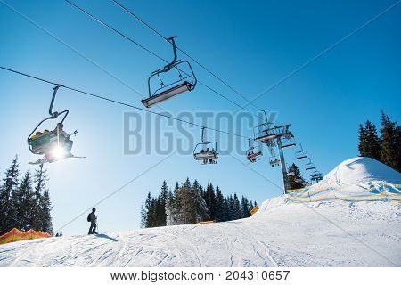 Silhouette Of Skier On Snowy Slope And Low Angle Shot Of A Ski Lift At Ski Resort In The Mountains O