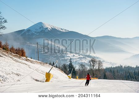 Beautiful Morning Landscape. Rear View Shot Of A Skier Skiing Down On The Slope In The Mountains On