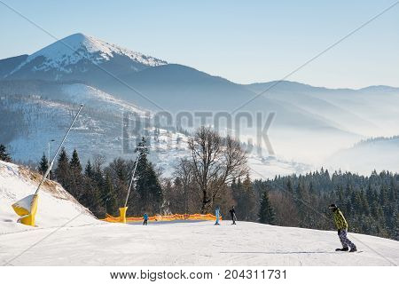 Shot Of A Skiers And Snowboarders Skiing On The Slope In The Mountains On A Beautiful Sunny Day Natu