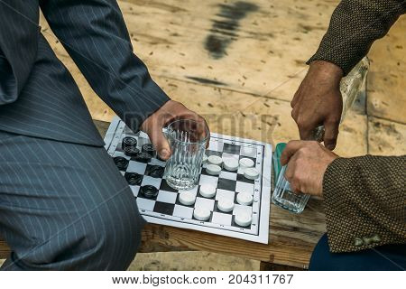 Close-up of two Russian men drinking vodka from cut glasses and playing checkers