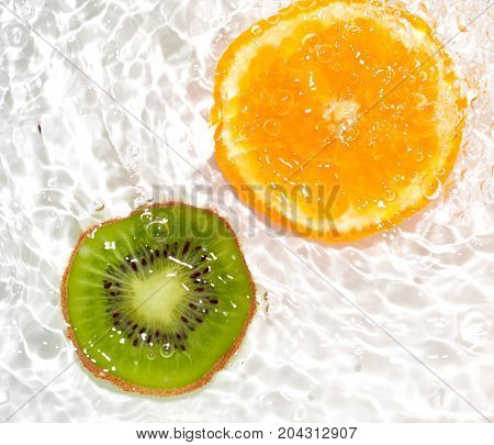 juicy kiwi and orange in water on a white background. macro