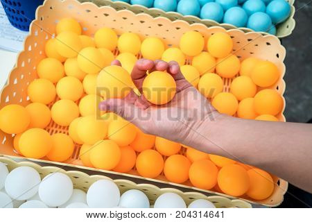 Woman hand holding two orange ping-pong balls.