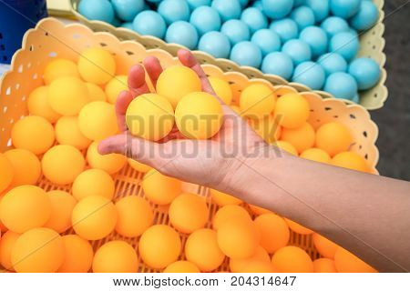 Woman hand holding three orange ping-pong balls.
