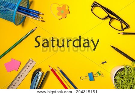 Top View of Saturday - word on yellow workplace with office or school supplies. Time Management and Schedule Concept.