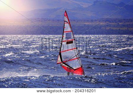 Sportman windsurfer on the lake surface at sunset time.