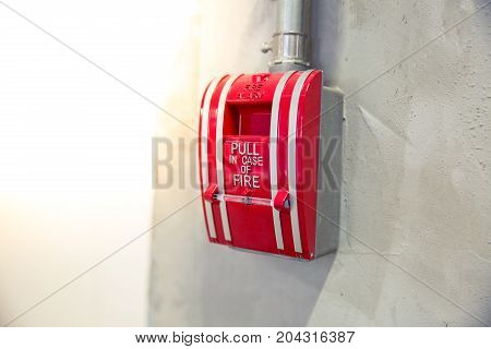 Selective focus on red gear alarm on the wall pull in case for call fire emergency fire alarm concept.