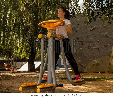 Young girl doing exercises for strengthening legs outdoor