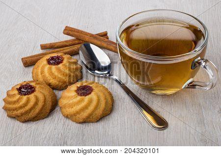 Cookies With Jam, Cinnamon Sticks, Cup Of Tea And Teaspoon