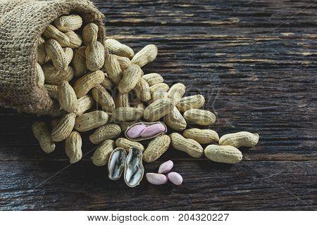 Peanuts in sack on wooden table. Peanut macro. Peanuts seed placed on peanuts.