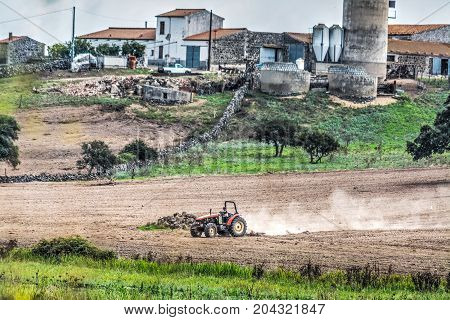Tractor ploughing a brown field in Sardinia Italy