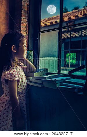 Asian Child Standing Near Window And Looking Aside While Feeling Sad.