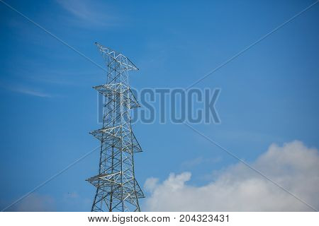 The building of the high voltage power pole no power line under construction has a blue sky background.