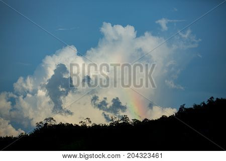 mountain range tropical rainforest canopy at southern of Thailand with more cloud sunset time with rainbow