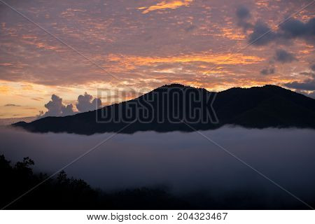 mountain range tropical rainforest canopy at southern of Thailand with more cloud sunset time