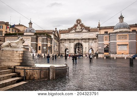 Rome Italy - October 31 2012: The main entrance of Piazza del Popolo - Porta del Popolo gate. Piazza del Popolo is a large urban square in Rome that many locals and tourists passing by everyday.