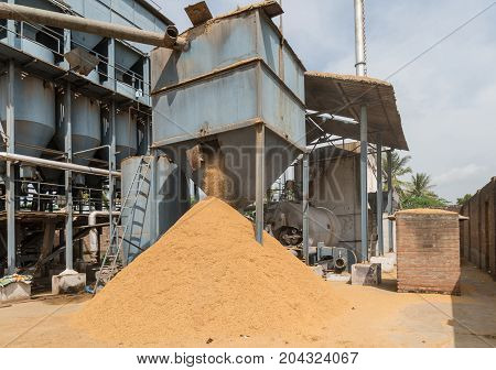 Mysore India - October 27 2013: In Ranganathapur the brown rice chaff falls on a heap out of a large square receptacle at an industrial rice miller. Husk is mechanically peeled from the rice kernel