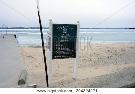 WEQUETONSING, MICHIGAN / UNITED STATES - MARCH 30, 2017: A sign provides the beach rules of the Wequetonsing Association Beach.