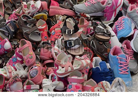 Kids shoes for sale at street market. Assorted pile of footwear.