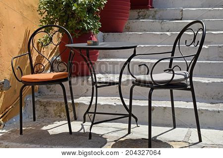 Two chairs and table at cafe bar in Greece.