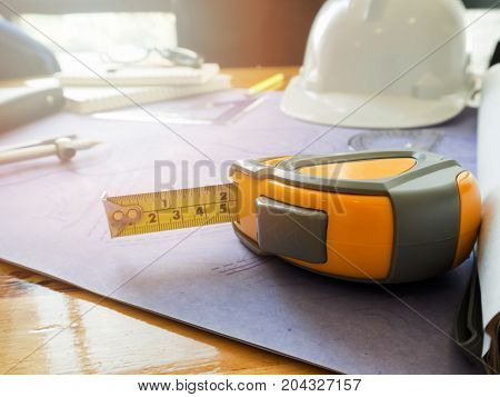 Yellow tape measure on blueprints. Architectural concept