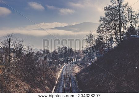 Wonderful perspective of railway line among slope mound covered in colorful tree and electric pole on left side with winter mountain range surrounding by fog mist and cloud under light blue sky background in Bled, Old railroad track in the middle of grey