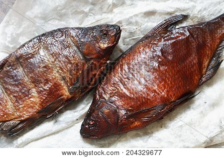 Closeup of pair freshness smoked breams on crumpled oiled paper