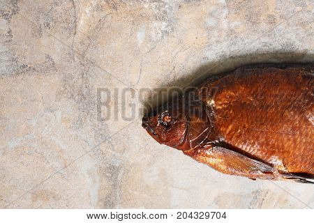 Closeup of one freshness smoked bream on stone background with free space