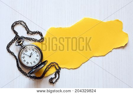 Piece of blank yellow paper for text near pocket watch on white wooden background