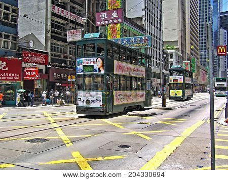 Central District, Hong Kong - March 25, 2003: A double-storey-tram runs through a street in Hong Kong, Central District.