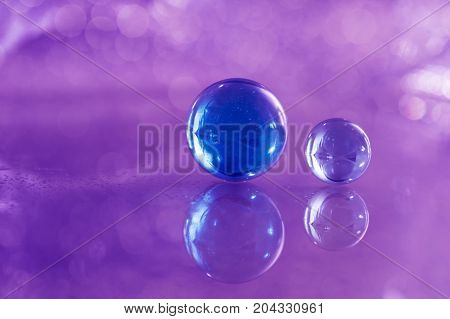 Two blue glass balls on a glass table. Glass balls on a purple background with reflection
