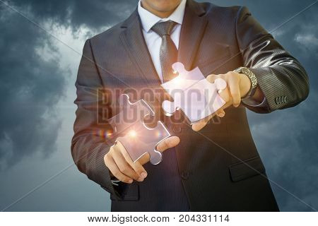 Businessman Connects Two Of The Puzzle In The Sky.